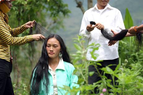 Một cặp vợ chồng chuyên mua tóc ở chợ phiên Tráng Kìm, Quản Bạ đang mua tóc của một cô gái người H'Mông (Ảnh: Lê Anh Tuấn)