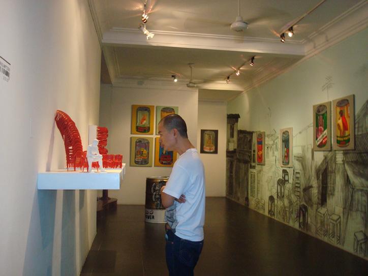 Bùi Công Khánh xem tác phẩm của mình - Ảnh Sàn Art