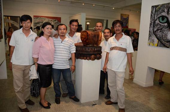 Điêu khắc gia Trần Mai Quốc Khánh (áo sọc ngang) cùng vợ và bạn bè bên tác phẩm của anh