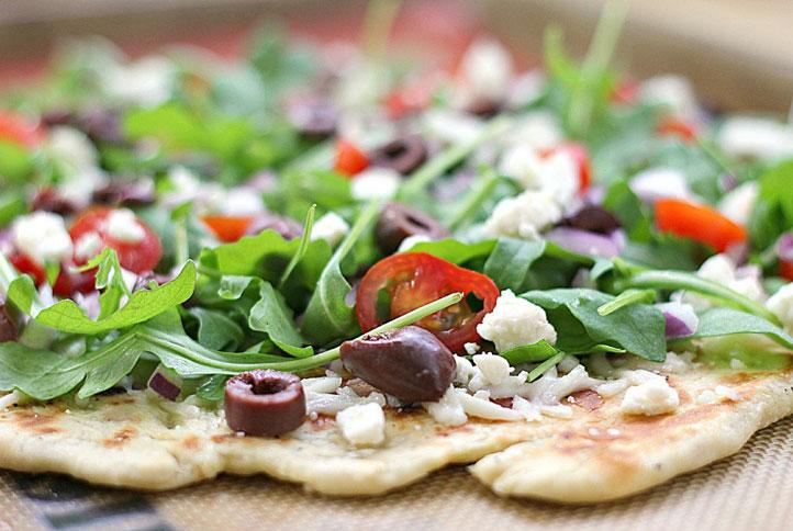 Bánh pizza rắc xa-lát rocket, cà chua bi, ô-liu nâu (nhỏ và ...