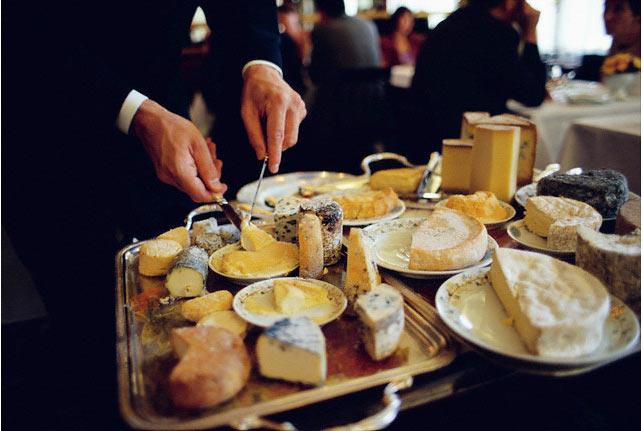 """Bồi đang phục vụ """"đủ thứ phó-mát"""" cho khách, các nhà hàng lớn lúc nào cũng có cả mâm phó-mát như thế, ai thích gì thì kêu."""