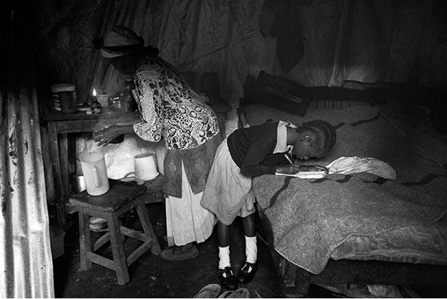 Ngoài đi tập võ, bà Gachenga chăm hai đứa cháu ngoại. Trong ảnh: bà đang chuẩn bị bữa sáng, còn cô cháu gài thì tranh thủ làm bài tập. Phụ nữ thuộc mọi lứa tuổi đều có nguy cơ bị quấy rối ở Korogocho, nhất là tại những khu toilet, khu nhà tắm công cộng.