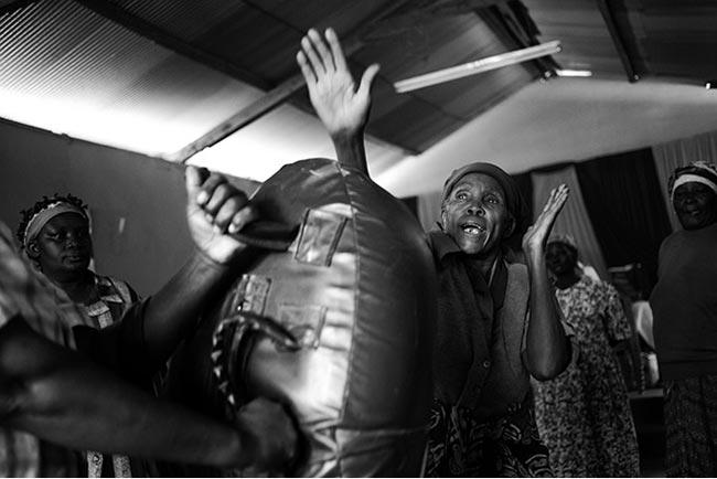 Bà Gachenga uýnh chiếc bao cát. Hiện nay, các vụ lạm dụng bà cụ có tuổi đang tăng, vì một số người tin rằng tỷ lệ cụ bà nhiễm HIV ít hơn phụ nữ trẻ rất nhiều, nên họ là một đối tượng cưỡng bức 'an toàn'