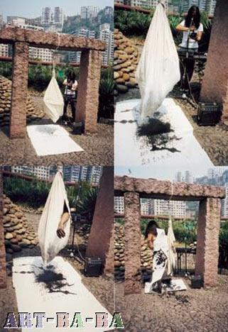 Zhoubin+Huanqing, 2002, Trùng Khánh: Cởi truồng giữ một cục nước đá làm bằng mực và bước vào một túi vải trắng treo lơ lửng. Huan Qing điều khiến các hộp loa cùng lúc phát ra những tiếng thở đau đớn của Zhou Bin (do lạnh). Mực tan và nhỏ qua cái túi xuống tờ giấy xuyến chỉ trắng trải trên nền đất.