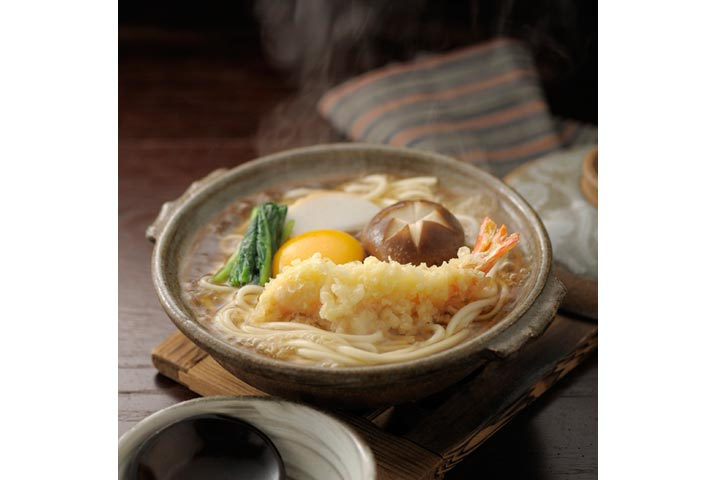 Món Nabeyaki udon ở Nhật, trên có tôm chiên, trứng sống, rau cải bó xôi, nấm, và chả cá cắt lát mỏng. Món này luôn nấu trong nồi đất.