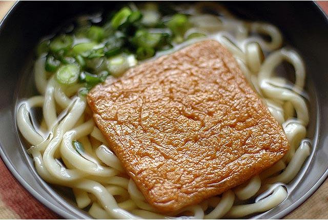 """Một loại udon phổ biến của Nhật: Udon ăn kèm với đậu hũ chiên, trên tô mì chỉ có thêm hành. Ít vậy nhưng ngon rồi, nước udon trông rất ngon, và đậu hũ sau khi chiên xong sẽ được hầm lại với nước tương – rất hợp với nước dùng udon vốn đã pha nước tương vào. Kể chuyện ngoài lề, món này tiếng Nhật gọi là Kitsune udon, mà kitsune lại có nghĩa là """"con cáo"""". Trong truyện manga hay phim anime, những con cáo (hoặc nhìn giống cáo như con Kompoko của truyện siêu nhân Mami), đều khoái ăn đậu hũ chiên; chung quy là bởi mấy món mì có đậu hũ chiên đều mang tên kitsune"""