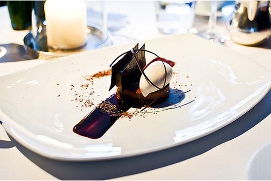 """Công việc mệt nhất của bồi bàn michelin là: phải bưng các món của mấy """"ông đầu bếp michelin"""" ra cho khách. Nghe thì tưởng dễ, nhưng mấy món nghệ thuật này vốn có lắm râu ria. Trong hình là món bánh sô-cô-la và kem tráng miệng của Per Se. Đầu bếp trang trí bằng mấy """"cọng"""" sô-cô-la mỏng te, bánh với kem thì """"đầy nguy cơ đổ ụp"""". Nếu không khéo và bưng mấy cái đĩa này nhưng bưng đĩa đồ nhậu; bánh, kem, với sô-cô-la gãy đổ khi vừa đặt xuống mặt khách là toi đời."""